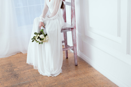 Foto de cropped view of elegant bride sitting on big chair with wedding bouquet - Imagen libre de derechos