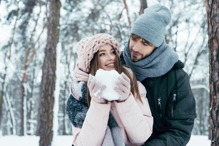 Photo pour young couple having fun together in snowy forest - image libre de droit
