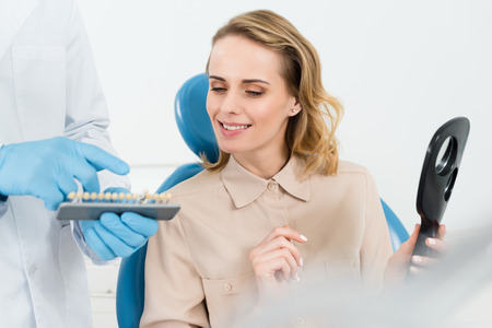 Photo for Doctor showing tooth implants to female patient in modern dental clinic - Royalty Free Image