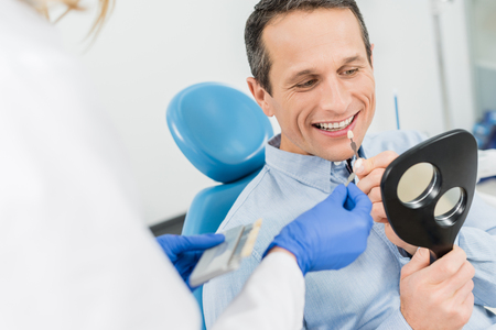 Foto de Male patient choosing tooth implant looking at mirror in modern dental clinic - Imagen libre de derechos