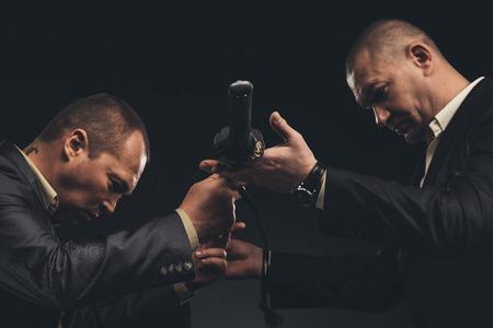 Photo pour Modern businessmen passing katana sword isolated on black - image libre de droit