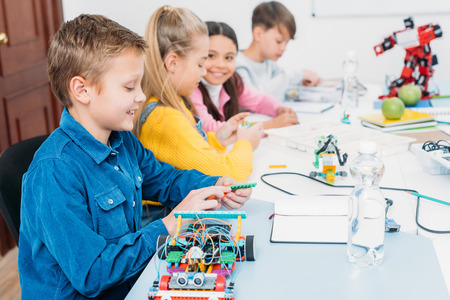 Photo pour happy children sitting at desk and making robots in stem education class - image libre de droit