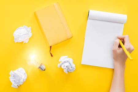 Foto de cropped view of woman writing in blank notebook, crumbled paper balls and glowing light bulb on yellow background, having new ideas concept - Imagen libre de derechos