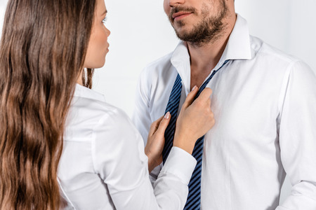 Photo for cropped image of girlfriend tying boyfriend tie in morning at home, social role concept - Royalty Free Image