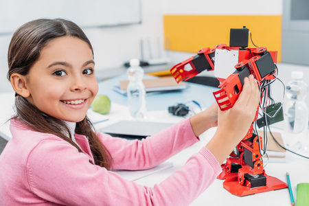 Foto de adorable schoolgirl sitting at table, holding robot model at STEM classroom and looking at camera - Imagen libre de derechos