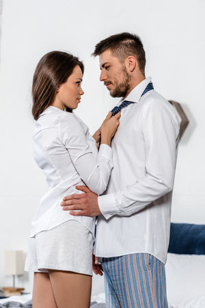 Photo for low angle view of girlfriend tying boyfriend tie in morning on weekday in bedroom, social role concept - Royalty Free Image