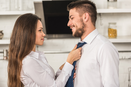 Photo for portrait of girlfriend tying smiling boyfriend tie in morning at kitchen, sexism concept - Royalty Free Image