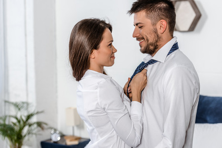 Photo for side view of cheerful girlfriend tying boyfriend tie in morning on weekday in bedroom, social role concept - Royalty Free Image
