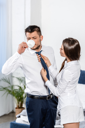 Photo for girlfriend tying boyfriend tie while he drinking coffee in morning at home, social role concept - Royalty Free Image