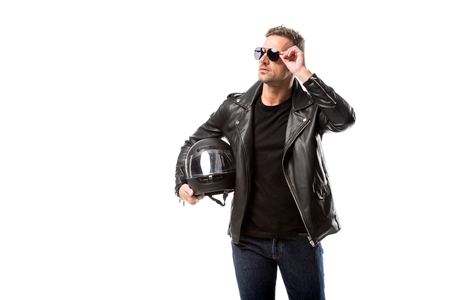 Foto de man in leather jacket and sunglasses holding motorcycle helmet and posing isolated on white - Imagen libre de derechos