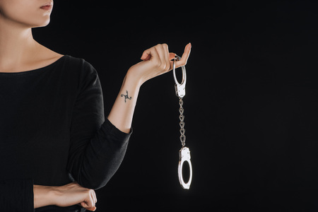 Photo for partial view of woman holding metal handcuffs isolated on black - Royalty Free Image
