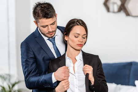 Photo for handsome boyfriend helping attractive girlfriend wearing jacket in morning at home - Royalty Free Image