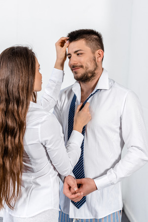 Photo for girlfriend tying boyfriend tie and touching his hair in morning on weekday in bedroom, social role concept - Royalty Free Image