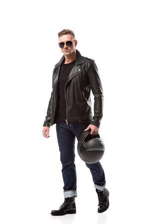 Foto de handsome man in leather jacket and sunglasses holding motorcycle helmet isolated on white - Imagen libre de derechos