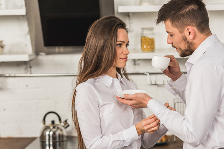 Photo for boyfriend drinking coffee and girlfriend buttoning his cuff at home, inequality concept - Royalty Free Image