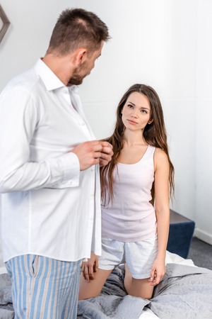 Photo for boyfriend buttoning shirt and looking at attractive girlfriend in morning at weekday, stereotypes concept - Royalty Free Image
