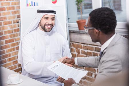 Foto de Multiethnic businessmen shaking hands and smiling in office - Imagen libre de derechos