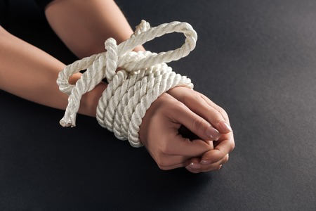 Foto de cropped view of female bound hands on black background - Imagen libre de derechos