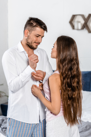 Photo for handsome boyfriend buttoning cuff and girlfriend buttoning his shirt in weekday morning in bedroom, social role concept - Royalty Free Image