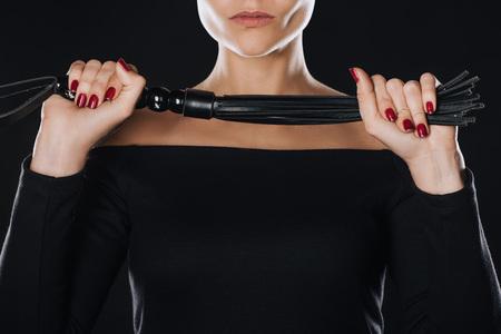 Foto de partial view of strict woman holding leather flogging whip isolated on black - Imagen libre de derechos