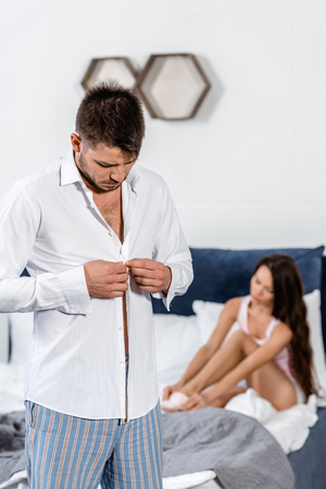 Photo for boyfriend buttoning shirt and preparing for work in morning at weekday, girlfriend wearing socks on bed, gender stereotypes concept - Royalty Free Image