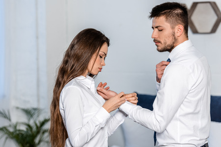 Photo for Side view of girlfriend buttoning boyfriend cuff in morning at home, sexism concept - Royalty Free Image