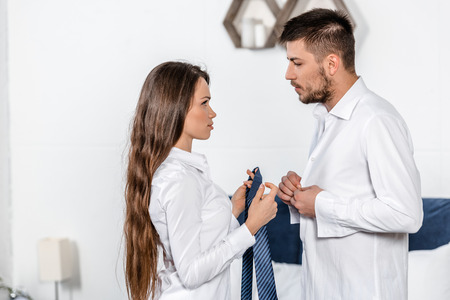 Photo for handsome boyfriend buttoning shirt, girlfriend holding his tie in weekday morning in bedroom, social role concept - Royalty Free Image