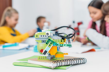 Photo for selective focus of handmade robot model and classmates working together on project during STEM lesson on background - Royalty Free Image