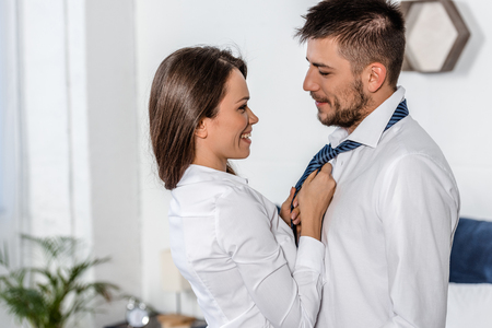 Photo for side view of smiling girlfriend tying boyfriend tie in morning on weekday in bedroom, social role concept - Royalty Free Image