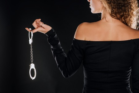 Photo for back view of curly woman holding silver handcuffs isolated on black - Royalty Free Image