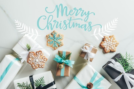 Foto de flat lay with christmas gift boxes and snowflake cookies on marble background with merry christmas lettering - Imagen libre de derechos