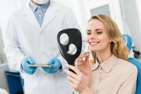 Photo for Woman choosing tooth implant looking at mirror in modern dental clinic - Royalty Free Image