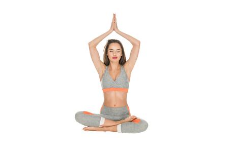 Foto de girl with closed eyes meditating in lotus position isolated on white - Imagen libre de derechos