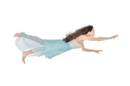 Foto de beautiful girl in dress levitating and looking away isolated on white - Imagen libre de derechos