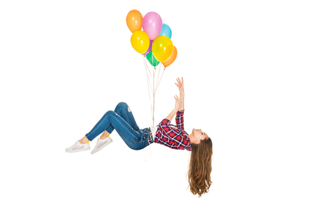 Foto de young woman levitating with colorful balloons isolated on white - Imagen libre de derechos