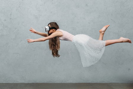 Foto de young barefoot woman in virtual reality headset levitating on grey - Imagen libre de derechos