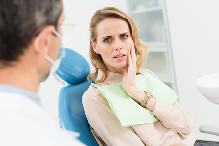 Photo for Female patient concerned about toothache in modern dental clinic - Royalty Free Image