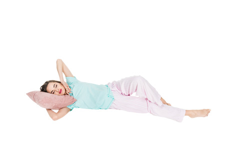 Foto de young woman in pajamas lying on pillow with closed eyes isolated on white - Imagen libre de derechos
