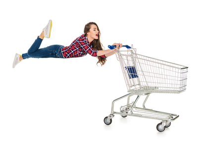 Foto de young woman levitating with empty shopping trolley isolated on white - Imagen libre de derechos
