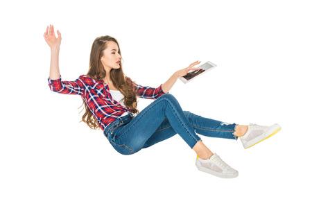 Foto de young woman using digital tablet while levitating isolated on white - Imagen libre de derechos