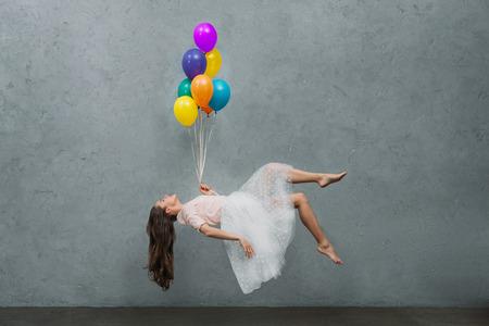 Foto de young woman levitating with colorful balloons - Imagen libre de derechos