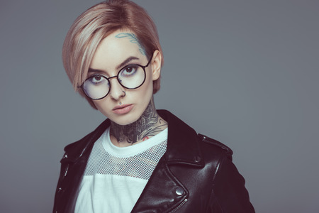 Photo pour tattooed girl with pink hair in eyeglasses and black leather jacket, isolated on grey - image libre de droit