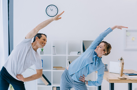Photo pour businesswoman doing side bend with trainer at office - image libre de droit