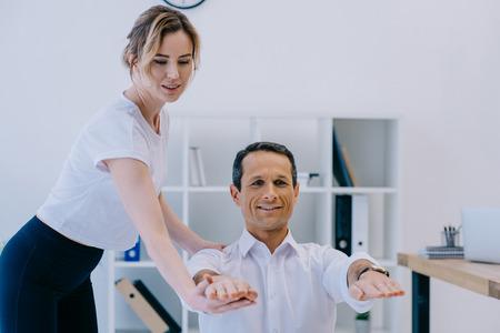Foto de handsome adult businessman doing exercise with trainer at office - Imagen libre de derechos