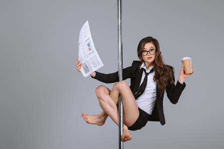 Foto de young businesswoman in eyeglasses holding newspaper and coffee to go, hanging on pole and looking at camera on grey - Imagen libre de derechos