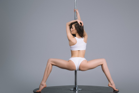 Foto de back view of young sporty woman in sportswear exercising with pole on grey - Imagen libre de derechos