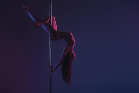 Foto de beautiful sensual flexible girl exercising with pole on blue - Imagen libre de derechos