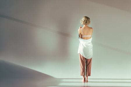 Photo pour back view of barefoot blonde girl in pink bra, shirt and pants standing in studio on grey - image libre de droit