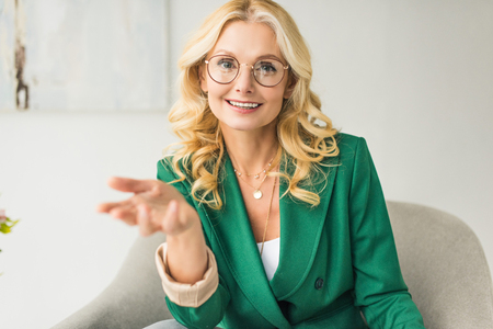 Foto de smiling middle aged businesswoman in eyeglasses looking at camera and gesturing with hand while sitting in armchair - Imagen libre de derechos