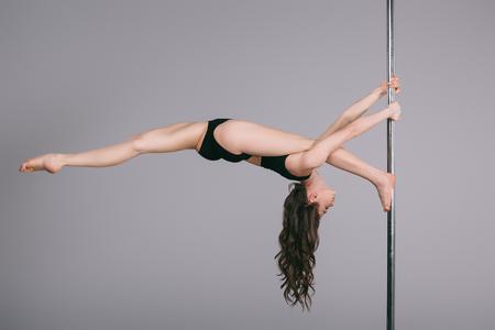 Foto de flexible sporty female dancer exercising with pole on grey - Imagen libre de derechos